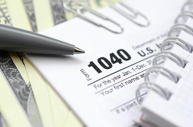 Der stift, das notizbuch und die dollarnoten liegen auf dem steuerformular 1040 us-einkommensteuererklärung.