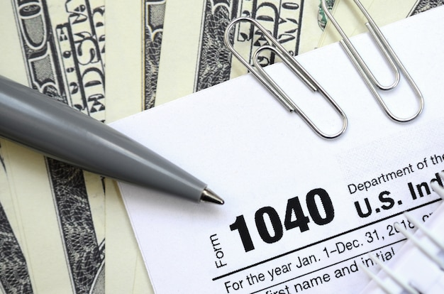 Der stift, das notizbuch und die dollarnoten liegen auf dem steuerformular