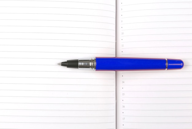 Der stift liegt auf einem offenen notizbuch. themen für wirtschaft und bildung