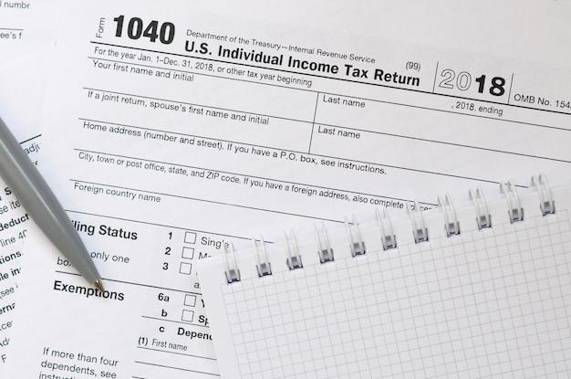 Der stift und das notizbuch liegen auf dem steuerformular 1040 us-einkommensteuererklärung