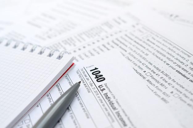 Der stift und das notizbuch liegen auf dem steuerformular 1040 us-einkommensteuererklärung.