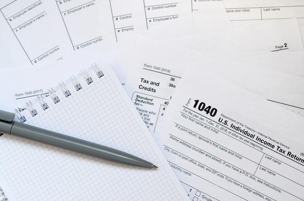 Der stift und das notizbuch liegen auf dem steuerformular 1040 us