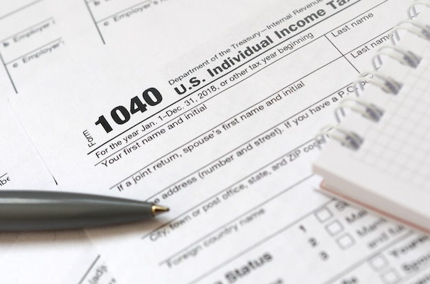 Der stift und das notizbuch liegen auf dem steuerformular 1040