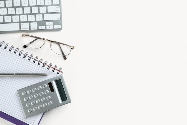Der stift und der taschenrechner befinden sich auf einem offenen notizblock. neben dem laptop und brille. artikel eines geschäftsmannes oder buchhalters auf einem leeren blatt des notizblocks. das konzept der finanz- und steuerberichterstattung.