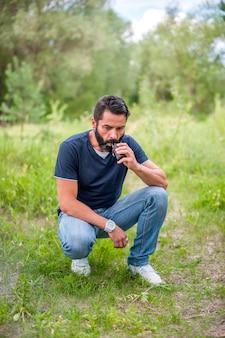 Der stilvolle bärtige mann ruht in der natur und dampft und lässt dampf von einer elektronischen zigarette ab. rauchen ohne tabak.