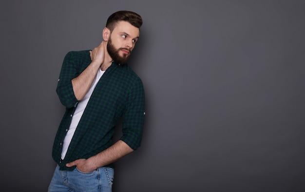 Der stilvolle, gutaussehende, bärtige mann der trendigen mode in der denimkleidung wirft auf