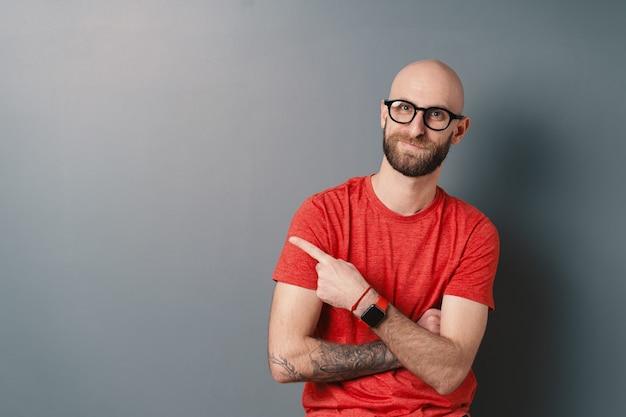 Der stilvolle junge bärtige mann, der seine schwarz gerahmte brille mit einer tätowierten hand repariert, während er lächelt