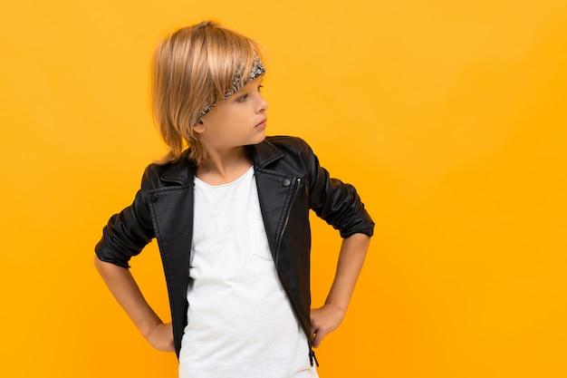 Der stilvolle junge junge in schwarzer jacke und weißem t-shirt legt die hände auf seine brust