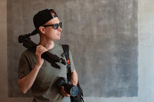 Der stilvolle junge männliche fotograf lässig gekleidete schwarze mütze mit sonnenbrille hält eine kamera und ein stativ vor dem hintergrund einer städtischen betonwand. fotografenkonzept