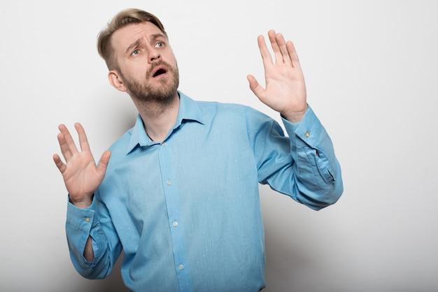Der stilvolle mann im blauen hemd schaut mit vor überraschung erhobenen händen weg