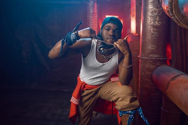 Der stilvolle rapper zeigt seinen goldschmuck im studio mit cooler underground-dekoration. hip-hop-performer, rap-sänger, breakdance