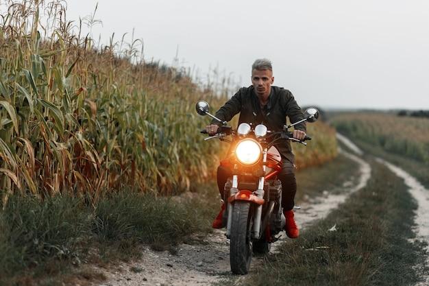 Der stilvolle schöne hipster-mann in der militärjacke fährt ein motorrad mit licht im feld