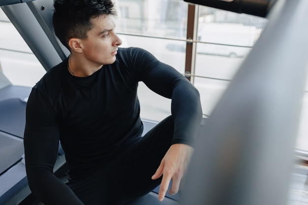 Der stilvolle typ im fitnessstudio ruht sich auf dem laufband aus. gesunder lebensstil.