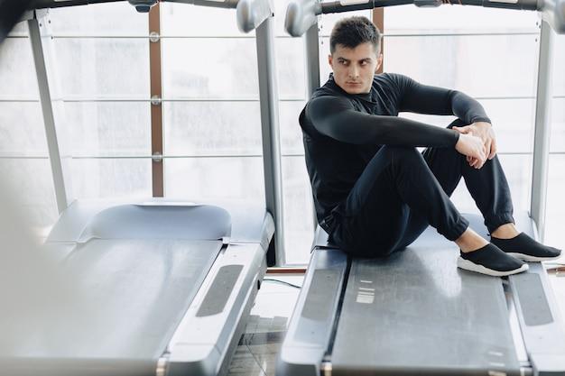 Der stilvolle typ im fitnessstudio sitzt auf dem laufband. gesunder lebensstil.