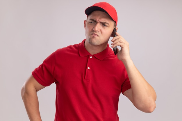 Der stirnrunzelnde blick auf den jungen lieferboten der seite, der uniform mit kappe trägt, spricht am telefon isoliert auf weißer wand