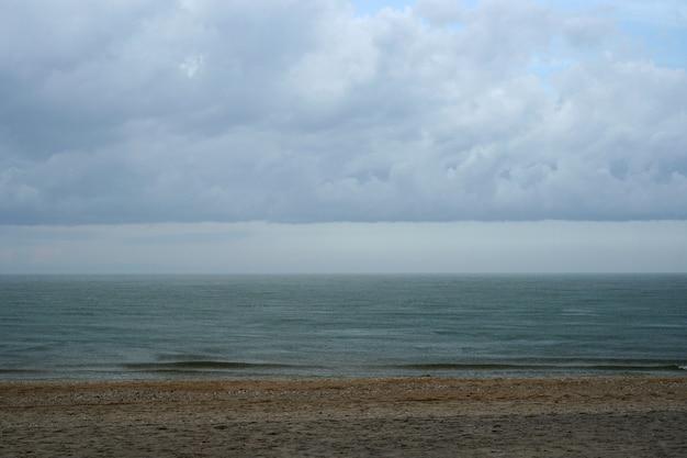Der strand mit meer und nimbuswolken am himmel