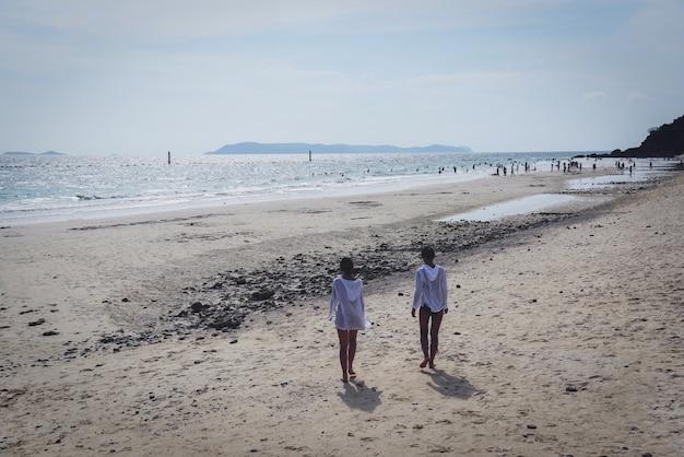 Der strandsommer mit touristen auf den inselfrauen, die auf den strand gehen