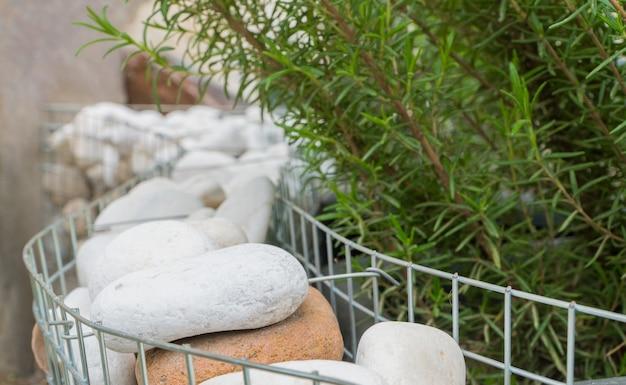 Der strauch ist mit runden steinen in einem metallgitter verziert. gartendekoration