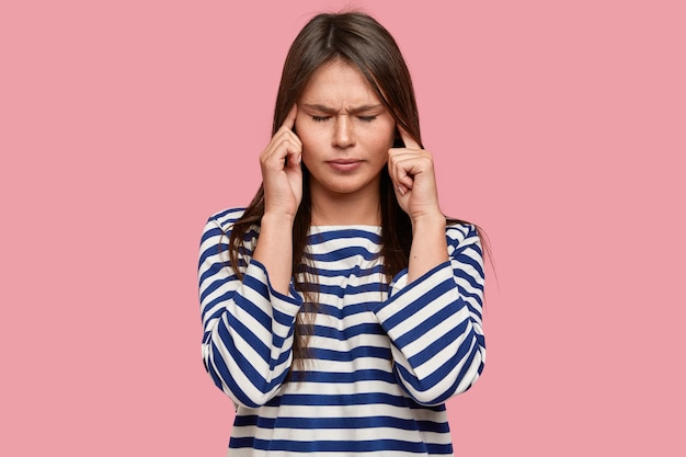 Der stressige, überarbeitete schüler hält die finger an den schläfen, hat einen missfallenen ausdruck und schließt die augen