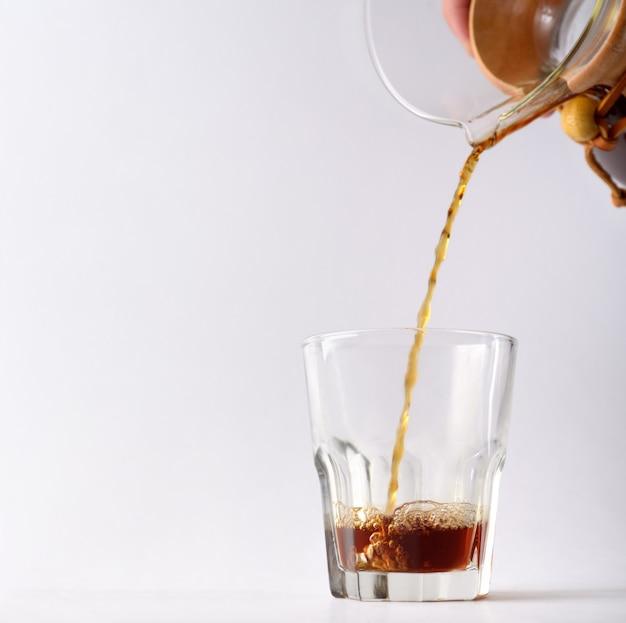 Der strom des heißen kaffeegetränks aus dem wird auf die glastasse gegossen, die auf dem leeren studiohintergrund isoliert ist. redaktioneller inhalt.