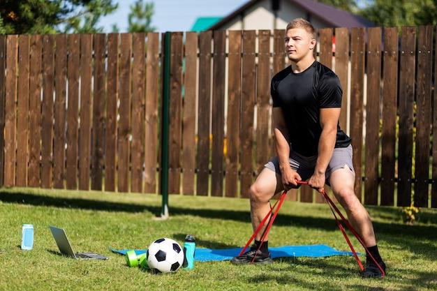 Der stromg-mann treibt sport im park. fröhlicher sportlicher mann mit blonden haaren macht eine kniebeuge mit gummi und uhren im laptop im garten