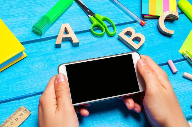 Der student hält ein mobiltelefon im hintergrund einer kreativen verwirrung auf dem desktop.