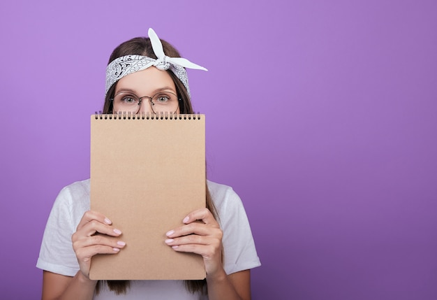 Der student hält ein notizbuch in der hand, ein album zum zeichnen.