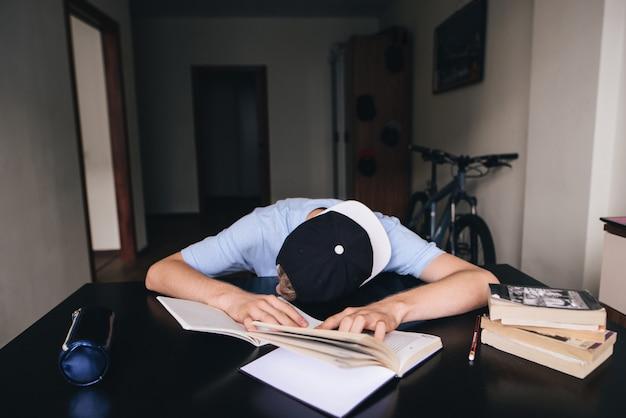 Der student schlief ein und machte hausaufgaben in büchern und notizbüchern in seinem zimmer. zu hause unterrichten. schlaf am tisch