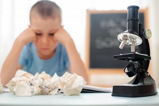 Der student sitzt am tisch und beschäftigt sich mit unterrichtsmaterial