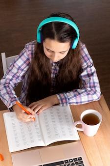 Der studentenlaptop, der anmerkung, hörende musikkopfhörer und lesebuch macht, trinken kaffee. e-learning-konzept.