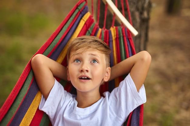 Der süße junge liegt in einer bunten hängematte. das kind reitet in einer hängematte. freizeitkonzept