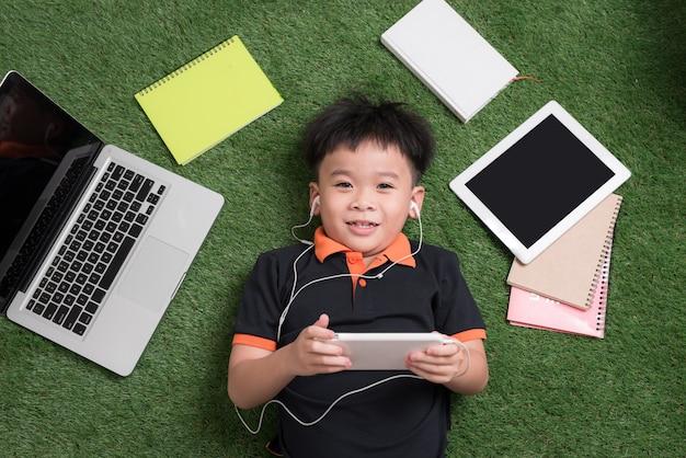 Der süße kleine junge hört mit seinem laptop, tablet und notebooks musik auf dem gras.