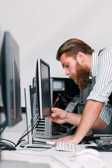 Der systemadministrator schaltet den computermonitor im büro ein. bartprogrammierer stecken elektronische geräte für die arbeit ein. business, programmierung, arbeitsplatzkonzept