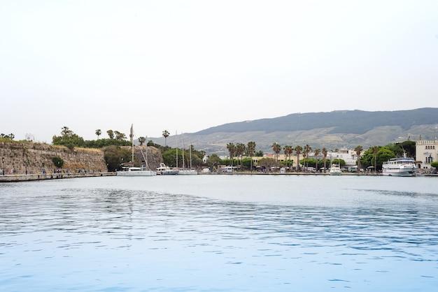 Der szenische hafen mit traditionellen ansichten der stadt, der palmen und der boote im dorf, kos griechenland