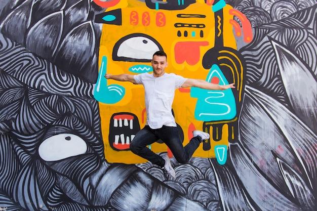 Der tänzer springend auf einen graffitihintergrund