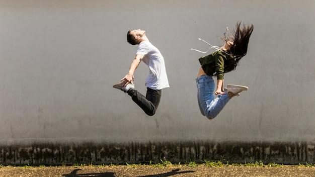 Der tänzer springend in einer luft gegen graue wand