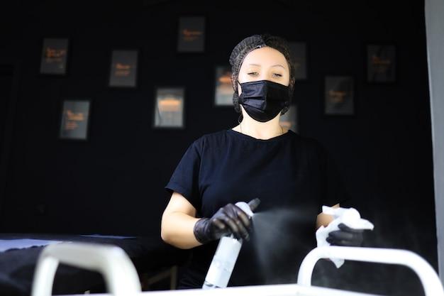 Der tätowierer desinfiziert die arbeitsfläche, führt vorbereitende arbeiten für das permanent make-up durch. tätowierer mädchen in schwarzer maske sägt desinfektionsmittel vor sich