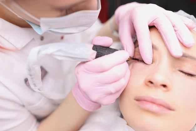 Der tätowierer trägt tinte auf das permanente augen-make-up-konzept der augenlider auf