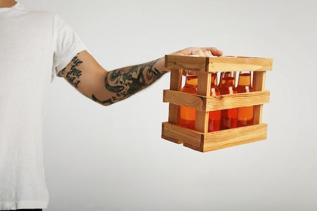 Der tätowierte lieferbote hält eine holzkiste mit sechs flaschen unbeschriftetem craft cider