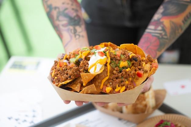 Der tätowierte straßenkoch hält die nachos-salsa in einem pappteller