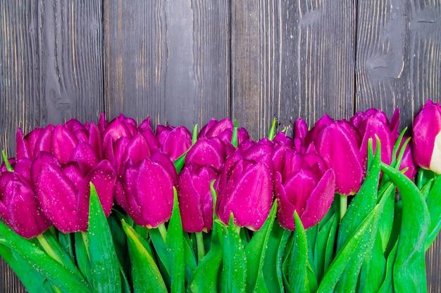 Der tageskopienraum der frauen mit hellen rosa tulpen auf einem schwarzen hölzernen hintergrund, beschaffenheiten
