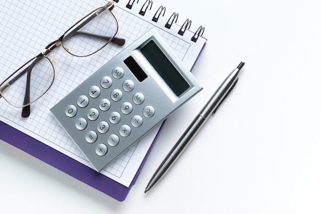 Der taschenrechner und die brille befinden sich auf einem offenen notizblock. neben dem stift. ein leeres blatt notizblock mit den aufzeichnungen eines geschäftsmannes oder buchhalters.