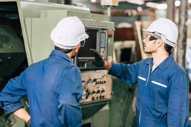 Der teamarbeiter des industrieingenieurs bedient eine schwere maschine mit einem computer-laptop, um die analyse des betriebsproblems zu unterstützen.