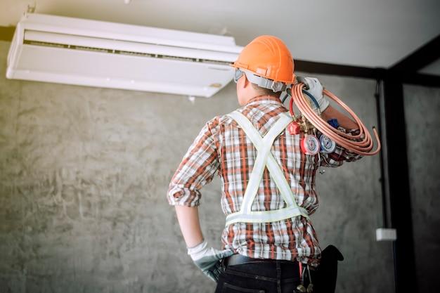 Der techniker der klimaanlage prüft und verwendet ideen, um die luft zu reparieren.