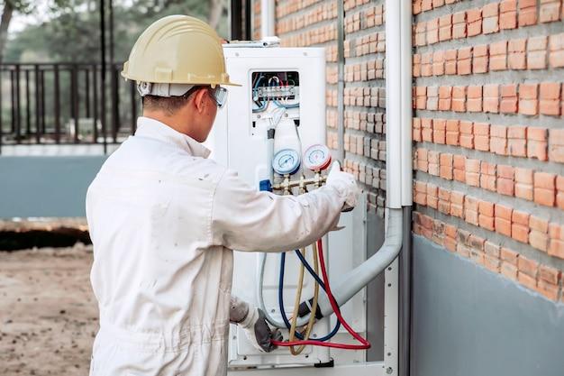 Der techniker der klimaanlage überprüft das luftkompressorsystem.