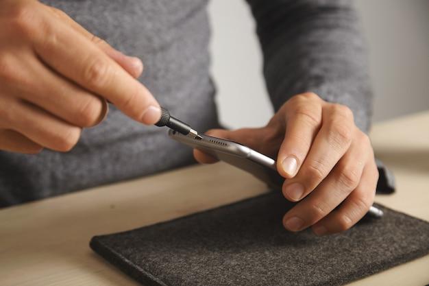 Der techniker löst mit dem treiber kleine schrauben am smartphone-gehäuse