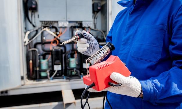 Der techniker repariert elektronische temperatursensoren mit einem elektronischen lötkolben