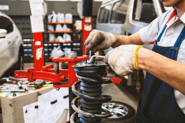 Der techniker repariert stoßdämpfer für kraftfahrzeuge mit weichzeichner und überlicht