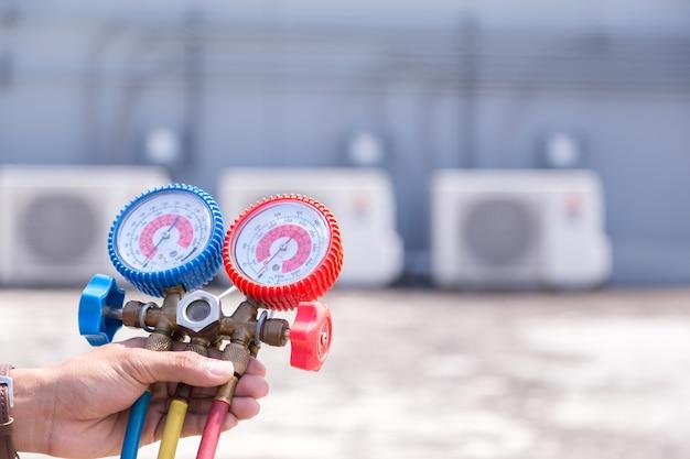 Der techniker überprüft die klimaanlage und die messgeräte zum befüllen der klimaanlagen.