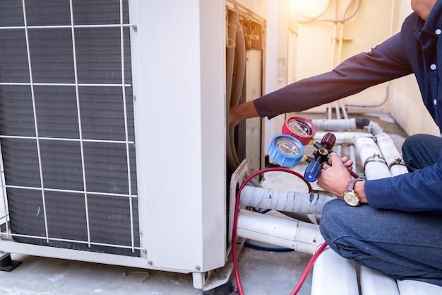 Der techniker überprüft die klimaanlage und misst die ausrüstung zum befüllen der klimaanlagen.
